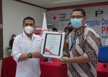 Ketua PMI Kota Makassar, Syamsu Rizal MI, memberikan penghargaan yang diterima langsung oleh Pemimpin Wilayah Pegadaian Kanwil VI Makassar, Zulfan Adam.